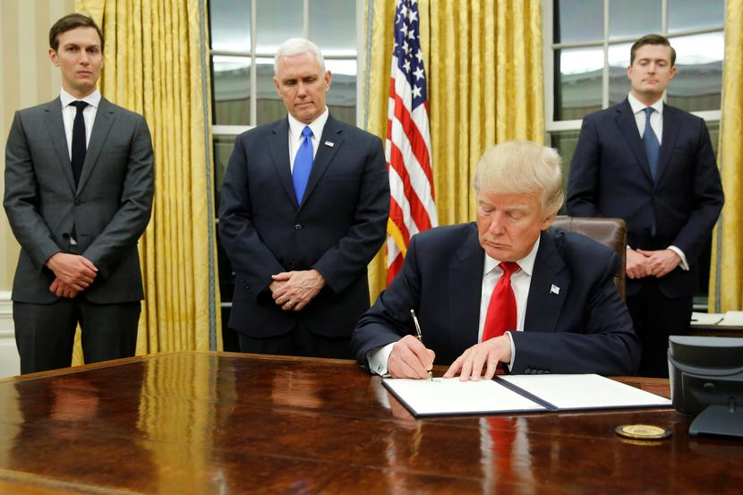 U.S. President Donald Trump, flanked by Senior Advisor Jared Kushner (standing, L-R), Vice President Mike Pence and Staff Secretary Rob Porter welcomes reporters into the Oval Office for him to sign his first executive orders at the White House in Washington, U.S. January 20, 2017. REUTERS/Jonathan Ernst     TPX IMAGES OF THE DAY